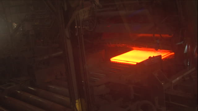 a glowing hot plate moves on a belt in and out of a cooling machine of a steel factory. - barren geld und finanzen stock-videos und b-roll-filmmaterial