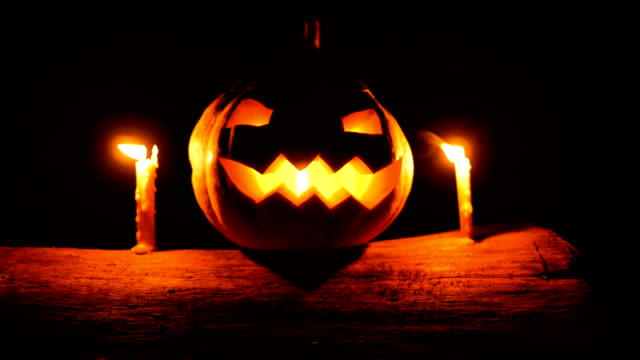 Glowing Jack-o-lantern with Candles on Tree Trunk in the Night, Dolly shot