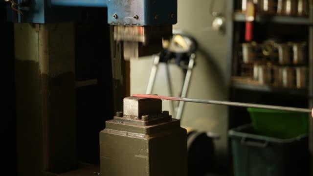 glowing metal object forged by power hammer - 鉄点の映像素材/bロール