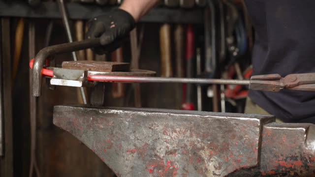 vídeos de stock e filmes b-roll de glowing metal object twisted on anvil with wrench - ferro metal