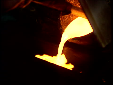 Glowing molten gold pouring into mold