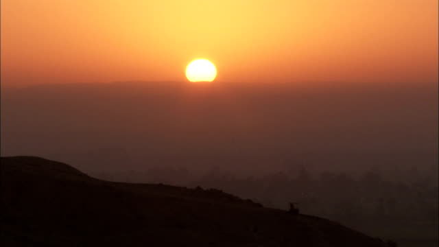 a glowing orange sun glows in a muted orange sky near deir el-bahari in egypt. available in hd. - tempio di hatshepsut video stock e b–roll
