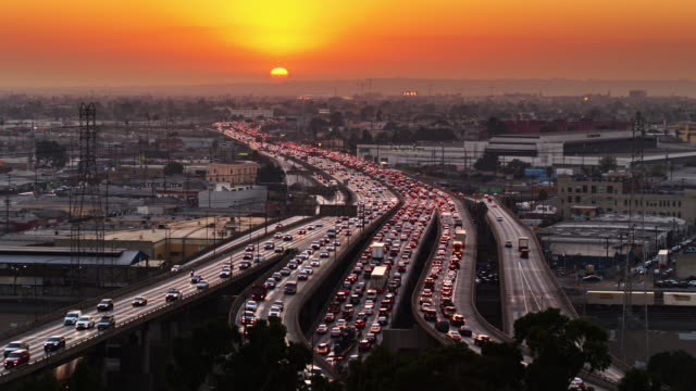 vídeos de stock e filmes b-roll de glowing orange sunset over la freeways - traffic jam