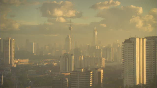 glowing sunlight shines on downtown kuala lumpur. - petronas twin towers stock videos & royalty-free footage