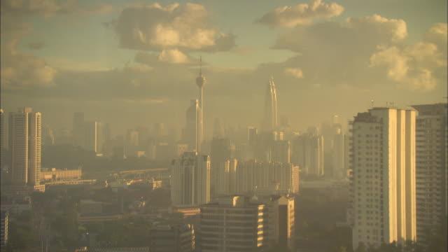 glowing sunlight shines on downtown kuala lumpur. - menara kuala lumpur tower stock videos & royalty-free footage