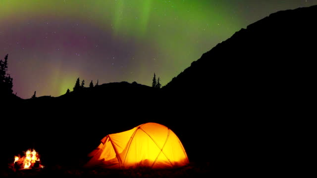 Glowing tent under the Northern Lights