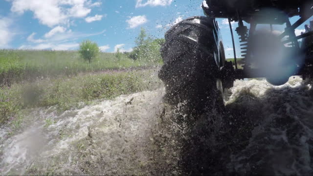 vídeos de stock e filmes b-roll de go pro on tractor tire as it rides through water and vegetation on farm - barro