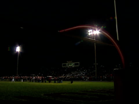 goal post in fg w/ stadium lights overhead in bg under night sky zi to crowd in bleachers cheering - football goal post stock videos and b-roll footage