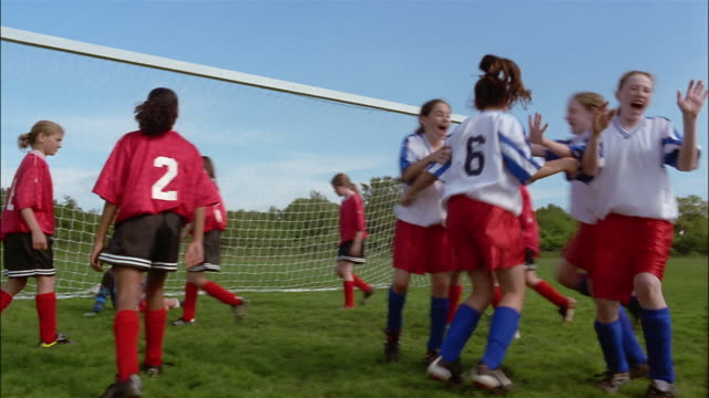 A goalie dives and misses the ball and the scoring team celebrates during a soccer game.