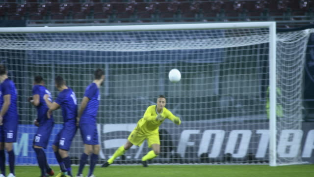 stockvideo's en b-roll-footage met slo mo goalkeeper defending the penalty kick done by red opponent - sportwedstrijd