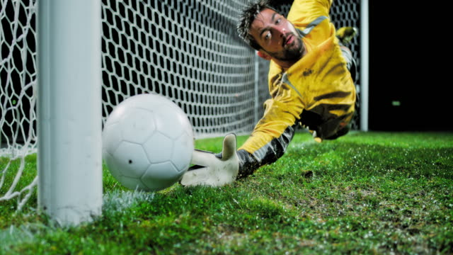 slo mo goalkeeper diving in to defend the goal - net sports equipment stock videos & royalty-free footage