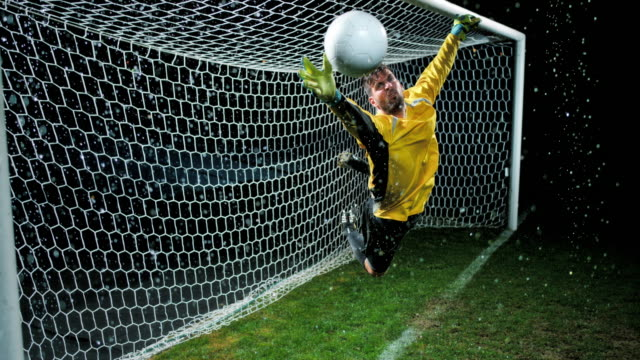 slo mo goalkeeper makes a dive to defend a goal - goalkeeper stock videos & royalty-free footage