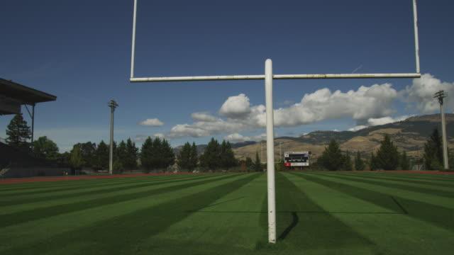 a goalpost casts a shadow across a freshly cut football field. - ゴールポスト点の映像素材/bロール