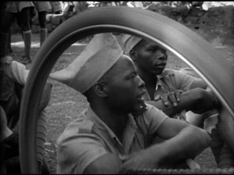 goan army african soldiers resting outdoors in shade by house one man working on upsidedown bicycle pedal sot singing 'salane' bike wheel turning vs... - imperium bildbanksvideor och videomaterial från bakom kulisserna