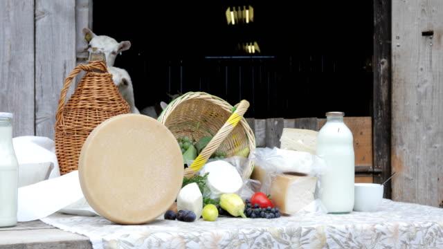 stockvideo's en b-roll-footage met geiten zuivelboerderij producten buiten op tafel met geiten in stal - dairy product
