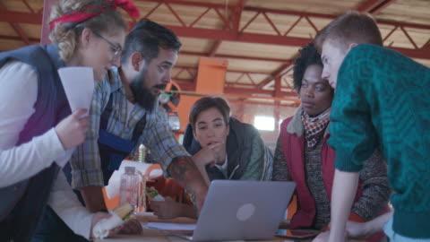 ヤギ農場の所有者と納屋で会議を持つボランティア - generation z点の映像素材/bロール