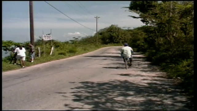 goat in grass and people riding past on bikes in jamaica - hooved animal stock videos and b-roll footage