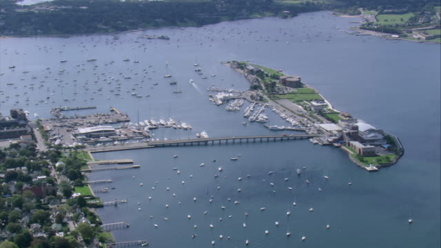 vídeos y material grabado en eventos de stock de aerial goat island and causeway bridge connecting to easton's point with numerous boats dotting the harbor / newport, rhode island, united states - formato buzón