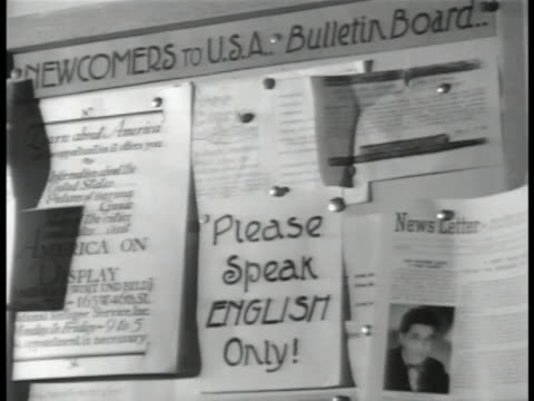 vídeos y material grabado en eventos de stock de god bless america' pennant on wall. newcomers bulleting board w/ 'please speak english only' posting. americanization class: group of adults reading... - las américas