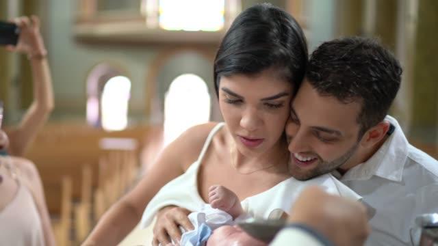 vidéos et rushes de parrains de dieu avec un bébé de filleul à la célébration de baptême - cérémonie