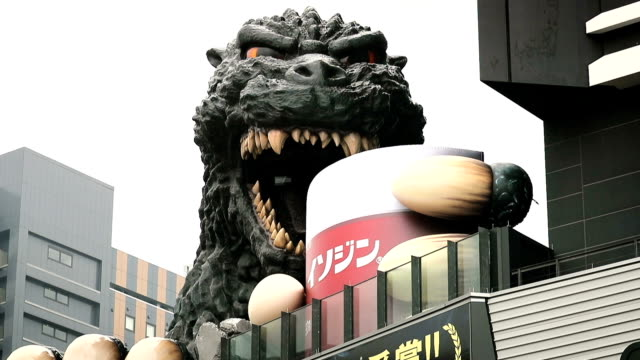 Godzilla looms large over Tokyo's Shinjuku district from an eightstory building but with a giant cup of mouthwash in its grasp humans need not fear...