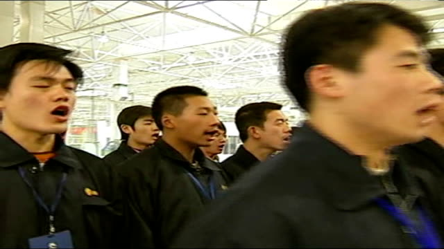 jiangsu province nanjing int chinese staff at new mg car manufacturing factory standing in rows as chant slogan and march away for lunchbreak - mittagspause stock-videos und b-roll-filmmaterial