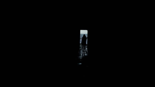 going to the beach. woman walking along dark corridor - fuggire video stock e b–roll