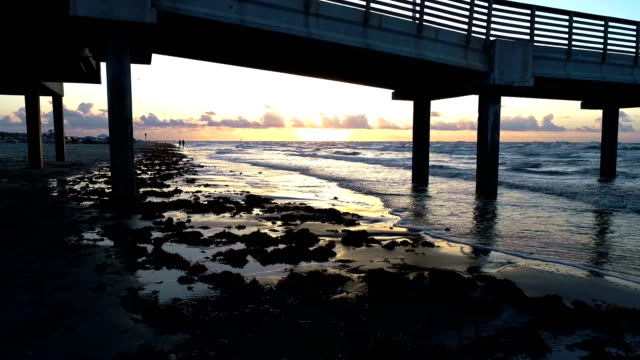 Going under the Pier with Sunrise in the background on Paradise beach during morning sunrise
