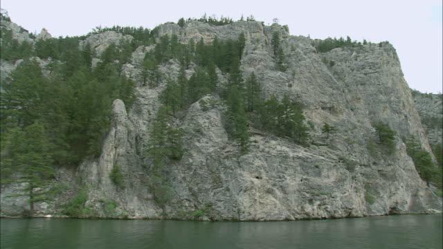 POV Going upstream on the Missouri River with pine-clad rugged mountains towering above / United States