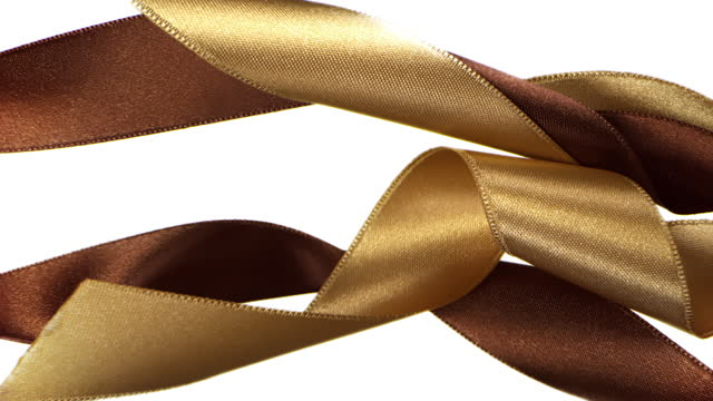 gold and brown colored ribbons on white background, for celebration events and party for new year, birthday party, christmas or any holidays, waiving and curling in super slow motion and close up - banner sign stock videos & royalty-free footage
