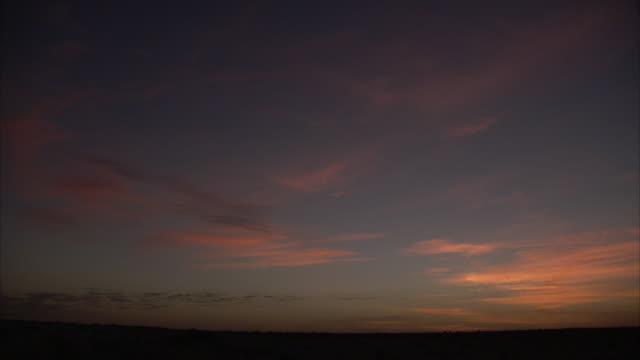 vídeos y material grabado en eventos de stock de gold and pink cirrus clouds hover over a dark landscape. - cirro