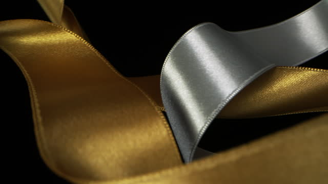 gold and silver ribbons on black background, for celebration events and party for new year, birthday party, christmas or any holidays, waiving and curling in super slow motion and close up - satin stock videos & royalty-free footage