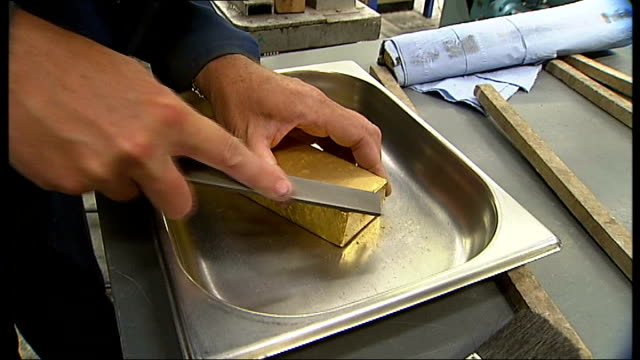 Gold bars being produced in factory Gold bar being manufactured and dipped in bucket / edges of gold bar being filed down / more of factory workers...