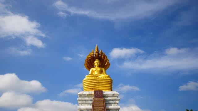 vídeos de stock e filmes b-roll de estátua de buda de ouro no fundo do céu time lapse - thailand