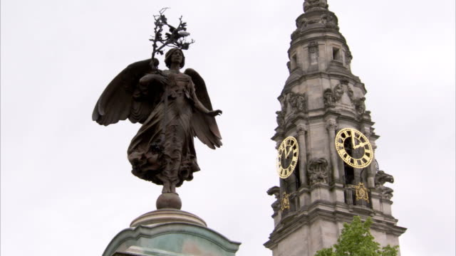 A gold clock accents the city hall clock tower in Cardiff, Wales. Available in HD.
