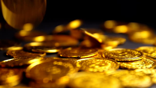 gold coins falling on black background - coin stock videos & royalty-free footage