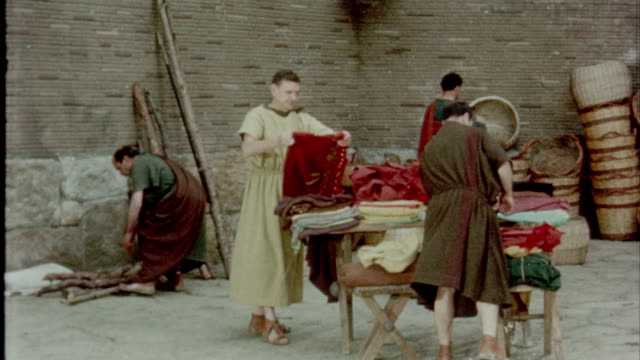 cu gold coins on table / men in trading industry moving pottery around folding fabrics / men and women in marketplace / men purchasing toga woman... - reenactment stock videos and b-roll footage