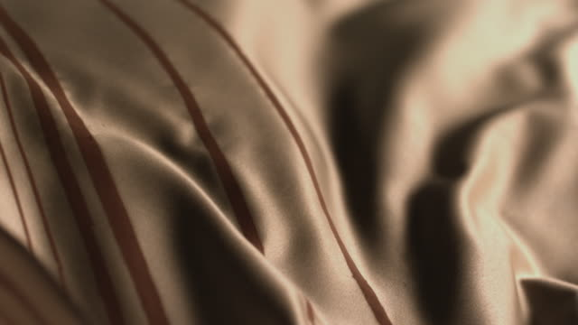 gold coloured silk scarf moving like waves from gentle wind. - textile stock-videos und b-roll-filmmaterial