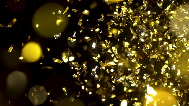 黒の背景に金紙吹雪ドロップ - gold colored点の映像素材/bロール