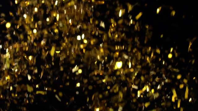 vidéos et rushes de explosion de confettis d'or sur le fond noir - paillette équipement d'art et d'artisanat