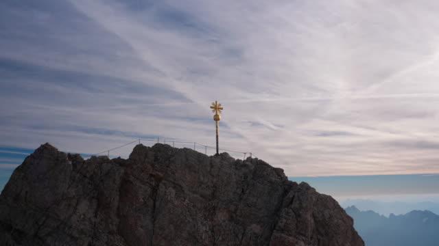 gold kreuz steht auf dem gipfel der zugspitze, deutschlands höchsten gipfel - kreuz religiöser gegenstand stock-videos und b-roll-filmmaterial
