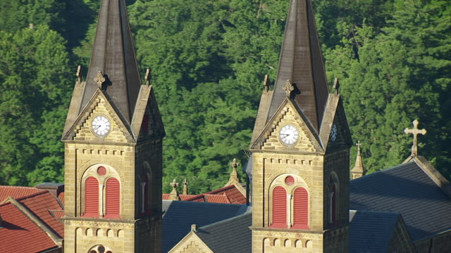 MS AERIAL POV Gold crosses atop clock towers of St. Meinrad Archabbey / Spencer County, Indiana, United States