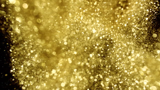 gold glitter exploding towards camera and becoming defocused on black background, shining bokeh - abundance stock videos & royalty-free footage