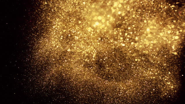 gold glitter exploding towards camera and becoming defocused on white background, sparkling bokeh - fascino video stock e b–roll
