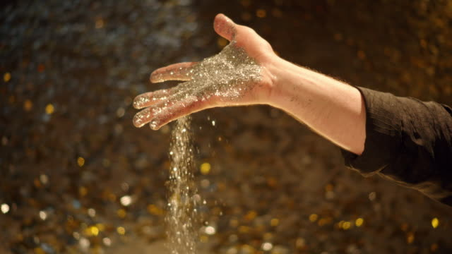 slo mo gold glitter falling out of hand - flitter stock-videos und b-roll-filmmaterial