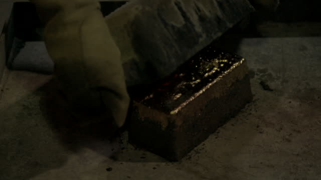 gold ingot is tipped out of mold - lingotto video stock e b–roll