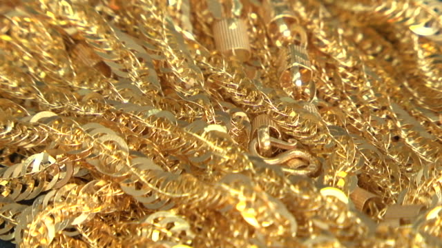 gold jewellery. rack-focus on thick strands of glittering gold link chains and necklaces in a jewellery box. - halskette stock-videos und b-roll-filmmaterial