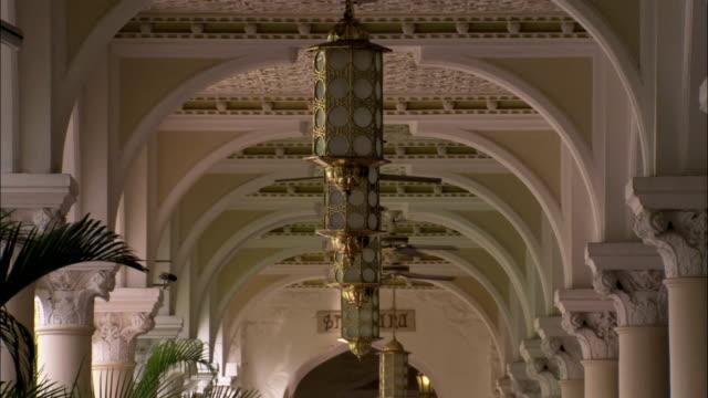 vídeos de stock, filmes e b-roll de gold lanterns and ceiling fans run the length of the covered walkway in the taj mahal hotel mumbai available in hd. - ventilador de teto