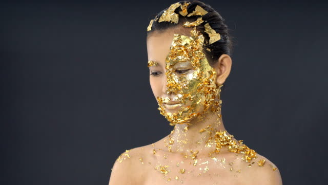 gold leaf high fashion style on asian woman face dark mystery look - gold leaf stock videos & royalty-free footage