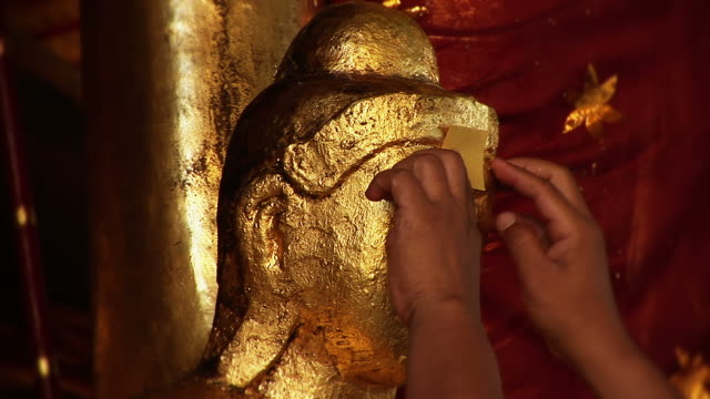 gold leaf stick to a buddha statue - gold leaf stock videos & royalty-free footage